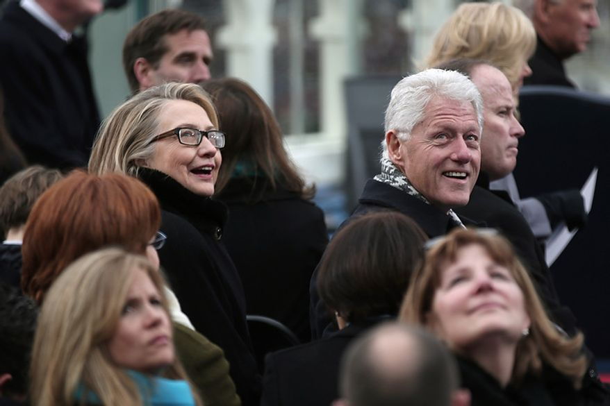 Secretary of State Hillary Clinton and former president Bill Clinton look on during the public ceremonial inauguration on the West Front of the U.S. Capitol January 21, 2013 in Washington, DC.   Barack Obama was re-elected for a second term as President of the United States.  (Photo by POOL Win McNamee/Getty Images)