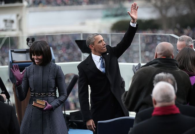 U.S. President Barack Obama waves after being sworn in by Supreme Court Chief Justice John Roberts as First lady Michelle Obama looks on during the public ceremonial inauguration on the West Front of the U.S. Capitol January 21, 2013 in Washington, DC.   Barack Obama was re-elected for a second term as President of the United States.  (Photo by POOL Win McNamee/Getty Images)