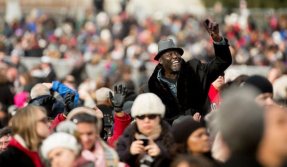 A man in the crowds waves before President Barack Obama is sworn in for his second term on the West Lawn of the U.S. Capitol Building at the 57th Presidential Inauguration Ceremony, Washington, D.C., Monday, January 21, 2013. (Andrew Harnik/The Washington Times)