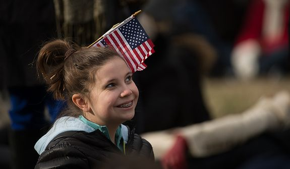 A young girl poses for a photo with an American flag in her hair before President Barack Obama is sworn in for his second term on the West Lawn of the U.S. Capitol Building at the 57th Presidential Inauguration Ceremony, Washington, D.C., Monday, January 21, 2013. (Andrew Harnik/The Washington Times)