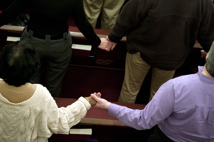 "Parishioners hold hands as they sing the song ""We Shall Overcome"" at the end of an interfaith service at Newtown Congregational Church in Newtown, Conn., Sunday, Jan. 20, 2013. (AP Photo/Jessica Hill)"