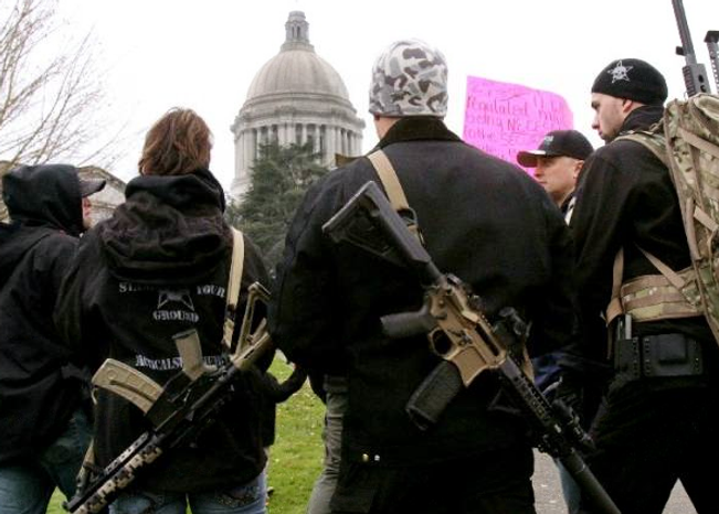 ** FILE ** Members of a Yakima, Wash., weapons seller carry firearms to a Second Amendment rally near the state Capitol i