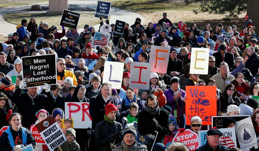 ** FILE ** Pro-life activists rally outside the Statehouse in Topeka, Kan., on Tuesday. (Associated Press)