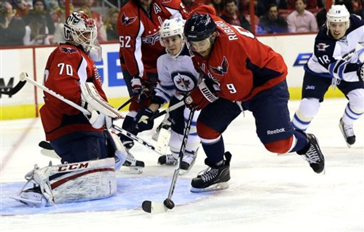 Washington Capitals center Mike Ribeiro (9) clears the puck as Winnipeg Jets center Mark Scheifele (55) and goalie Braden Holtby (70) watch, in the third period of an NHL hockey game Tuesday, Jan. 22, 2013 in Washington. The Jets won 4-2. (AP Photo/Alex Brandon)