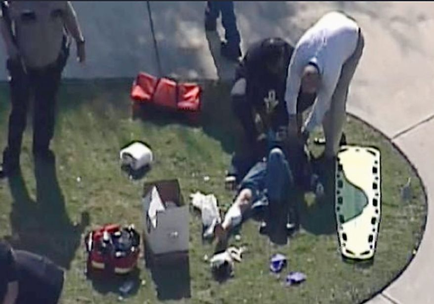 Emergency personnel attend to an unidentified person at Lone Star College on Tuesday, Jan. 22, 2013, in Houston. Law enforcement officials say the community college is locked down amid reports of a shooter on campus. (AP Photo/Courtesy of KPRC-TV)