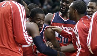 Washington Wizards guard Jordan Crawford, middle, is mobbed by teammates after sinking a three point shot at the buzzer to win an NBA basketball game against the Portland Trail Blazers in Portland, Ore., Monday, Jan. 21, 2013. Crawford came off the bench to score 13 points to beat the Trail Blazers 98-95.(AP Photo/Don Ryan)