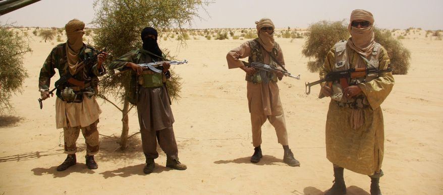 Militants from the Islamist terrorist group Ansar Dine stand guard during a hostage handover in the desert outside Timbuktu, Mali, in April. (Associated Press)