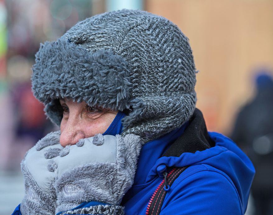 Chloe Elms, visiting D.C. from San Diego, holds her hands close to her face to try to stay warm in Chinatown on Wednesday. D.C. area residents have been bundled up since Tuesday after weekend temperatures in the 50s. (Andrew S. Geraci/The Washington Times)