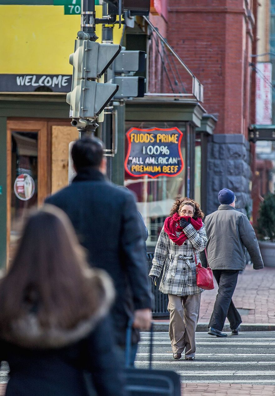 Scarves, gloves, hats and heavy coats have been brought out of closets and donned for outdoor wear. A woman does her best to protect her face from the cold while walking through Chinatown in D.C. on Wednesday. (Andrew S. Geraci/The Washington Times)