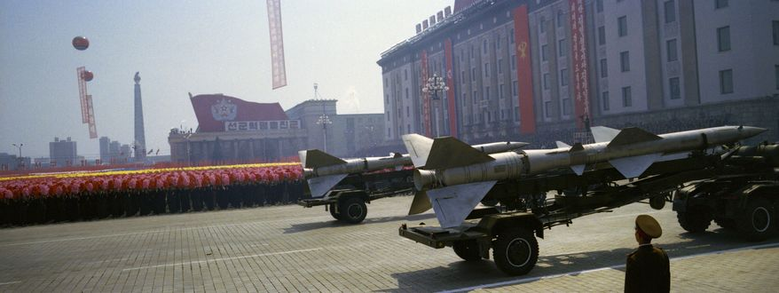 **FILE** North Korean rockets roll past flower-waving civilians and a soldier standing at attention April 15, 2012, during a mass military parade in Pyongyang's Kim Il Sung Square to celebrate 100 years since the birth of the late North Korean founder Kim Il Sung. (Associated Press)