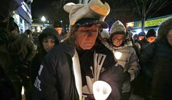 Kim Gasper (center), of Bellefonte, Pa., attends a candlelight memorial in State College, Pa., on Jan. 22, 2013, the first anniversary of the death of former Penn State head football coach Joe Paterno. (Associated Press)