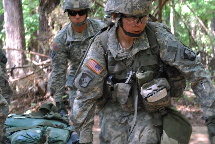 **FILE** Capt. Sara Rodriguez, 26, of the 101st Airborne Division, carries a litter of sandbags during the Expert Field Medical Badge training at Fort Campbell, Ky., on May 9, 2012. (Associated Press)