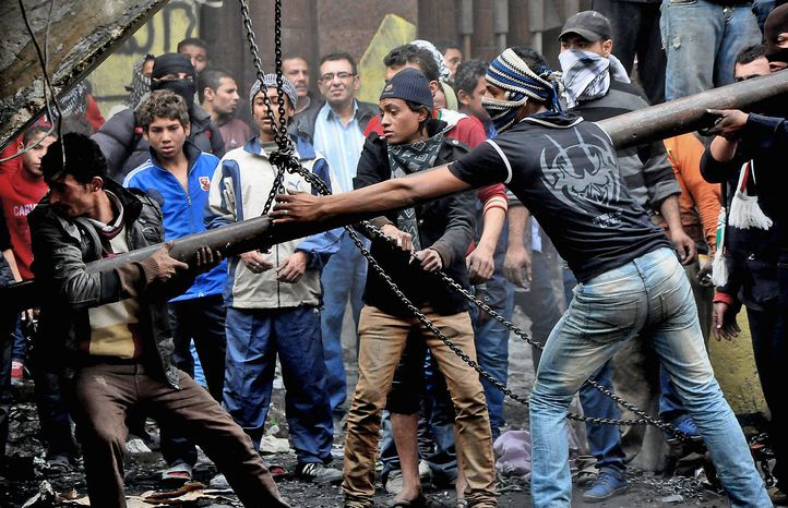Egyptian protesters try to tear down a cement wall built to prevent them from reaching parliament and the Cabinet building near Tahrir Square in Cairo on Jan. 24, 2013. (Associated Press)