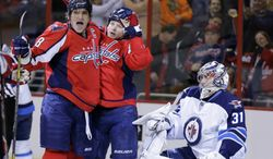 Washington Capitals left wing Alex Ovechkin (8) from Russia celebrates with center Matt Hendricks (26,) after Henricks' goal past Winnipeg Jets goalie Ondrej Pavelec (31) from the Czech Republic, in the first period of an NHL hockey game Tuesday, Jan. 22, 2013 in Washington. (AP Photo/Alex Brandon)