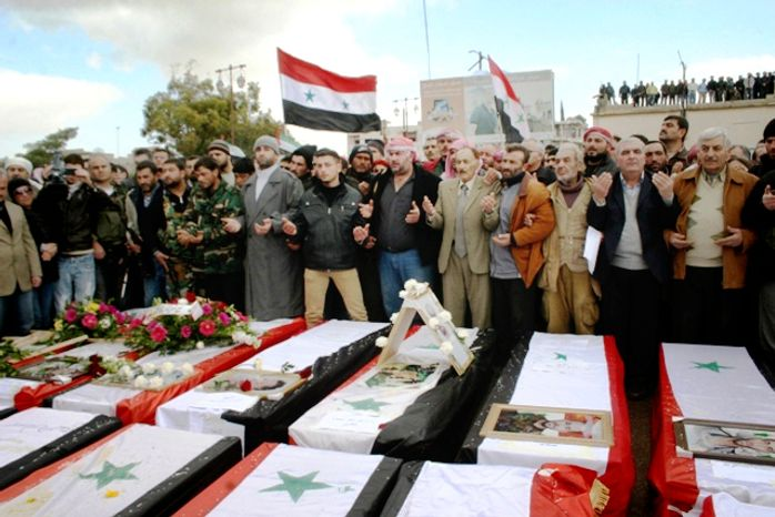 On Wednesday, Jan. 23, 2013, Syrians take part in a funeral procession for those killed in a car-bomb explosion at a headquarters of a pro-government militia late Monday in the central Syrian town of Salamiya in Hama province. (AP Photo/SANA)