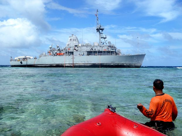 ** FILE ** In this Jan. 22, 2013, photo released by the Philippine Coast Guard, coast guard divers approach the USS Guardian, a U.S. Navy minesweeper, to assess the situation after it ran aground last week off Tubbataha Reef, a World Heritage Site in the Sulu Sea, 640 kilometers (400 miles) southwest of Manila, Philippines. (AP Photo/Philippine Coast Guard)