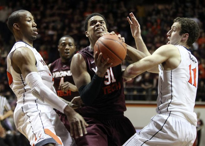 Virginia Tech's Jarell Eddie (31) drives against Virginia's Akil Mitchell (25) and Evan Nolte (11) during the second half of their NCAA college basketball game on Thursday, Jan. 24, 2013, in Blacksburg, Va. Virginia won 74-58. (AP Photo/The Roanoke Times, Matt Gentry)