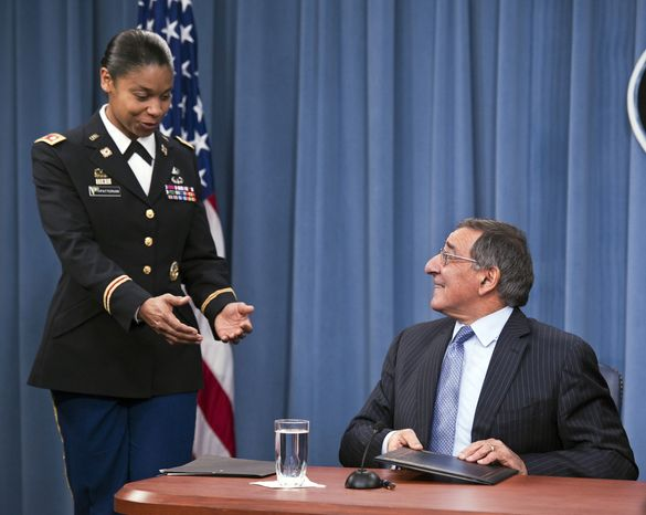 Army Lt. Col. Tamatha Patterson of Huntingdon, Tenn., waits for Defense Secretary Leon E. Panetta to hand her the memorandum he has just signed ending the 1994 ban on women serving in combat on Jan. 24, 2013, during a news conference at the Pentagon. (Associated Press)