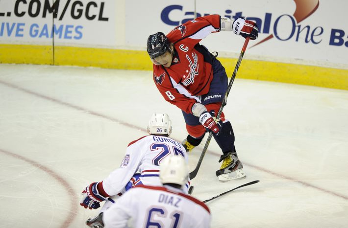 Washington Capitals left wing Alex Ovechkin (8), of Russia, shoots the puck against Montreal Canadiens defensemen Josh Gorges (26) and Raphael Diaz (61) during the second period of the Canadiens' 4-1 win on Jan. 24, 2013, in Washington. (Associated Press)