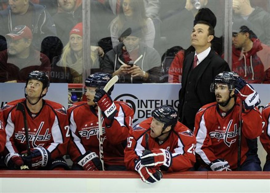 Washington Capitals head coach Adam Oates, standing right, looks up during the first period of an NHL hockey game against the Montreal Canadiens, Thursday, Jan. 24, 2013, in Washington. (AP Photo/Nick Wass)