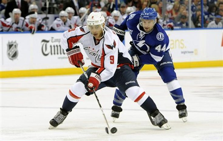 Washington Capitals center Mike Ribeiro, left, controls the puck against Tampa Bay Lightning center Nate Thompson during the first period of an NHL hockey game Saturday, Jan. 19, 2013, in Tampa, Fla. (AP Photo/Brian Blanco)