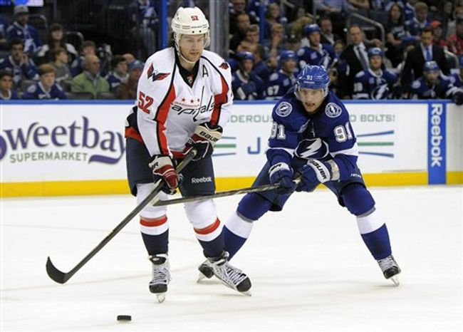 Washington Capitals defenseman Mike Green, left, works against Tampa Bay Lightning center Steven Stamkos during the second period of an NHL hockey game Saturday, Jan. 19, 2013, in Tampa, Fla. (AP Photo/Brian Blanco)