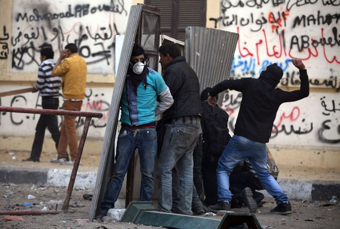Egyptian protesters take cover as they clash with riot police, not seen, near Tahrir Square, Cairo, Egypt, Friday, Jan. 25, 2013. Two years after Egypt's revolution began, the country's schism was on display Friday as the mainly liberal and secular opposition held rallies saying the goa
