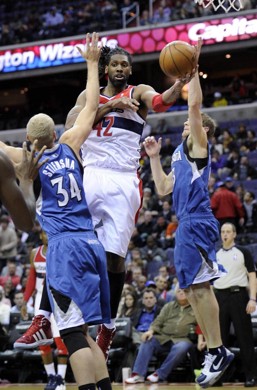 Washington Wizards center Nene (42), of Brazil, passes the ball against Minnesota Timberwolves center Greg Stiemsma (34) and Luke Ridnour, right, during the second half of an NBA basketball game on Friday, Jan. 25, 2013, in Washington. The Wizards won 114-101. (AP Photo/Nick Wass)