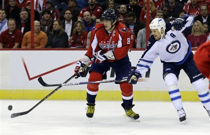 Washington Capitals left wing Alex Ovechkin (8) from Russia, battle for the puck with Winnipeg Jets center Olli Jokinen (12) from Finland, in the first period of an NHL hockey game Tuesday, Jan. 22, 2013 in Washington. (AP Photo/Alex Brandon)