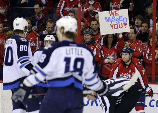 """A fan holds a sign """"We Missed You,"""" as Karl Alzner of the Washington Capitals looks on. (AP Photo/Alex Brandon)"""