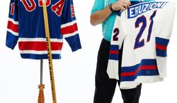 "Mike Eruzione, the captain of the 1980 ""Miracle on Ice"" Olympic hockey team, poses with the game sweaters and stick he  putting up for auction."