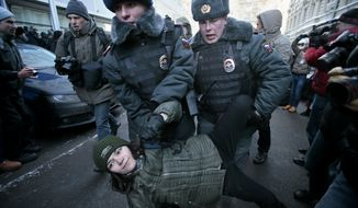 """Police detain a gay rights activist during a protest near the State Duma, Russia's lower parliament chamber, in Moscow on Jan. 25, 2013. A controversial bill banning """"homosexual propaganda"""" was submitted to Russia's lower house of parliament for the first of three hearings. Twenty people were detained, according to a police report. (Associated Press)"""