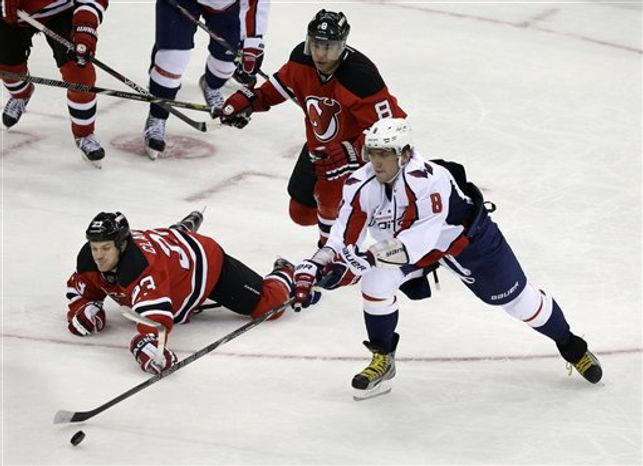 New Jersey Devils' David Clarkson (23) falls to the ice as Washington Capitals' Alex Ovechkin, of Russia, (8) slaps the puck away during overtime in an NHL hockey game Friday, Jan. 25, 2013, in Newark, N.J. The Devils won 3-2. (AP Photo/Mel Evans)