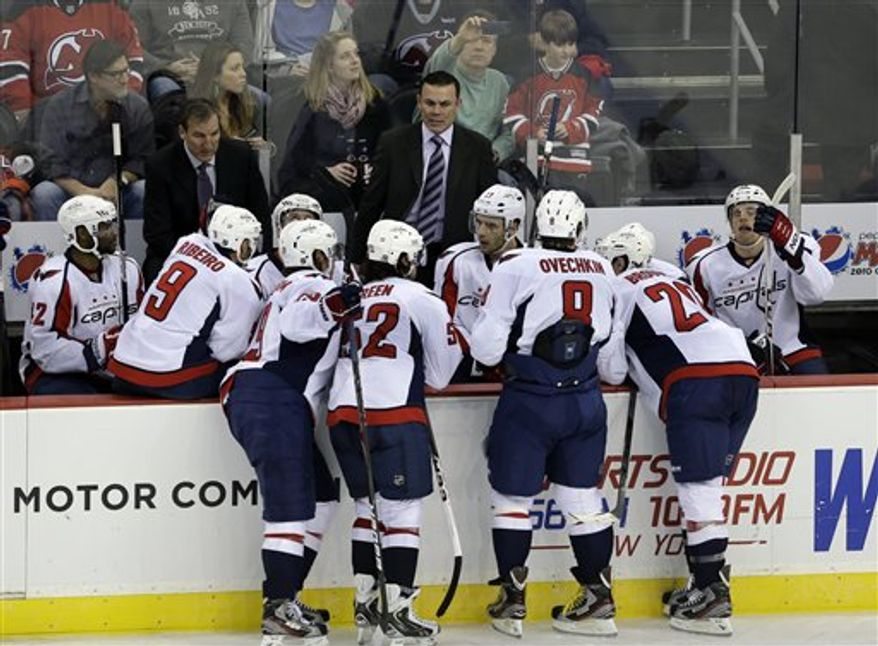 Washington Capitals head coach Adam Oates, center, talks to his players during overtime in an NHL hockey game against the New Jersey Devils Friday, Jan. 25, 2013, in Newark, N.J. The Devils won 3-2. (AP Photo/Mel Evans)
