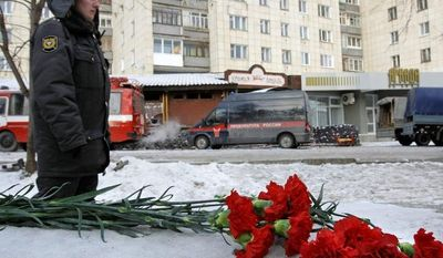A police officer stands guard next to flowers placed on the snow in front of the Lame Horse nightclub on Dec. 5, 2009, in Perm, Russia, where a fire broke out after pyrotechnics set plastic and decorative twigs on a ceiling ablaze, killing 152 people. (Associated Press)