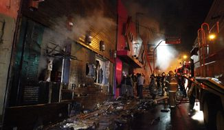 Firefighters work to extinguish a fire at the Kiss nightclub in Santa Maria, Brazil, on Sunday, Jan. 27, 2013. (AP Photo/Agencia RBS)