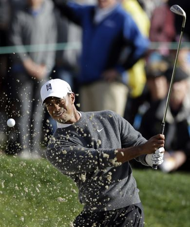 Tiger Woods hits out of a bunker on the 18th hole during the third round of the Farmers Insurance Open golf tournament at the Torrey Pines Golf Course, Sunday, Jan. 27, 2013, in San D
