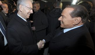 Italian Premier Mario Monti (left) and former Premier Silvio Berlusconi shake hands in Milan on Sunday, Jan. 27, 2013. (AP Photo/Antonio Calanni)