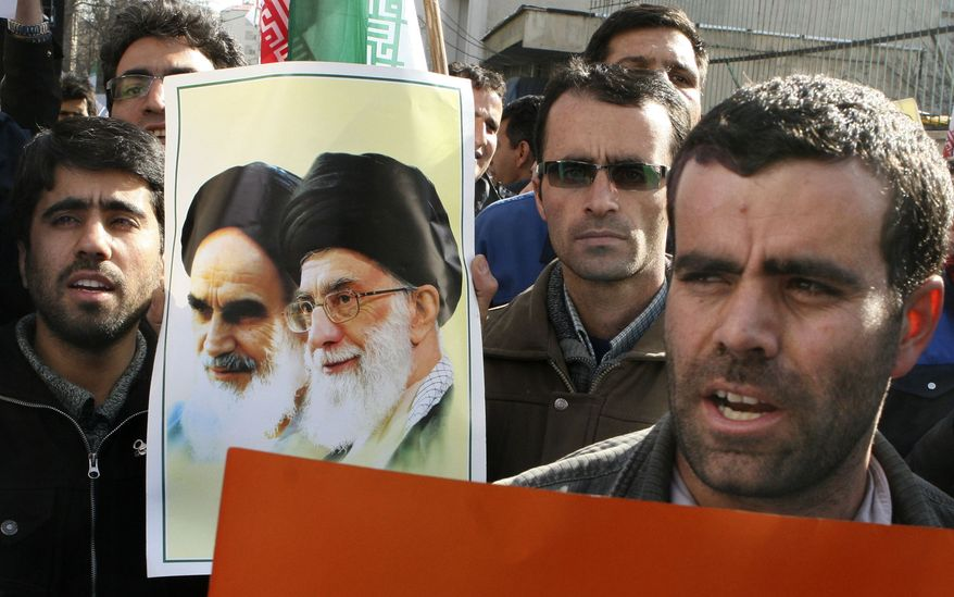 Workers of the Entekhab Industrial Group chant slogans as they hold a poster showing Iran's late revolutionary founder, Ayatollah Khomeini (left), and the current supreme leader, Ayatollah Ali Khamenei, during a protest in front of the South Korean Embassy in Tehran on Sunday, Jan. 27, 2013. (AP Photo/Vahid Salemi)