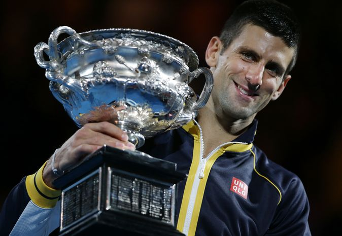 Serbia's Novak Djokovic holds his trophy after defeating Britain's Andy Murray in the men's final at the Australian Open tennis championship in Melbourne, Australia, Sunday, Jan. 27, 2013. (AP Photo/Aaron Favila)