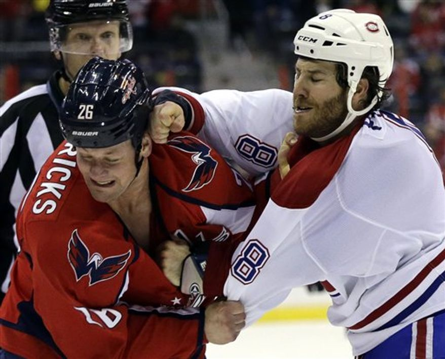 Washington Capitals center Matt Hendricks (26) is hit by Montreal Canadiens right wing Brandon Prust (8) during a fight in the third period of an NHL hockey game on Thursday, Jan. 24, 2013, in Washington. The Canadiens won 4-1. (AP Photo/Alex Brandon)
