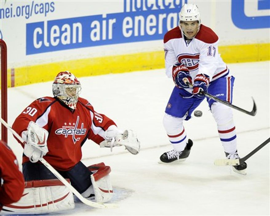 Montreal Canadiens left wing Rene Bourque (17) swats at the puck against Washington Capitals goalie Michal Neuvirth (30), of the Czech Republic, during the second period of an NHL hockey game on Thursday, Jan. 24, 2013, in Washington. (AP Photo/Nick Wass)