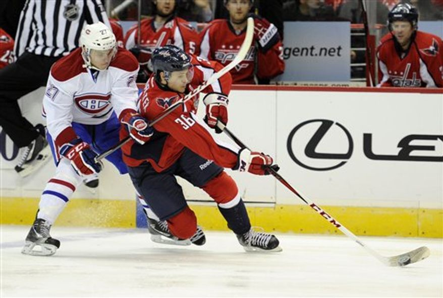 Montreal Canadiens center Alex Galchenyuk (27) battles with Washington Capitals defenseman Tomas Kundratek (36), of the Czech Republic, for the puck during the third period of an NHL hockey game on Thursday, Jan. 24, 2013, in Washington. The Canadiens won 4-1.(AP Photo/Nick Wass)