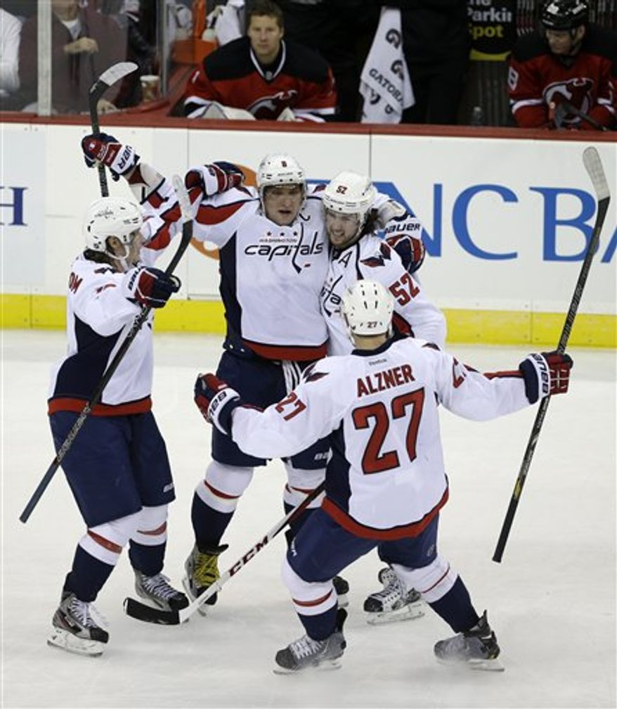 Washington Capitals' Alex Ovechkin, of Russia, (8), Karl Alzner (27) and Nicklas Backstrom (19), left, celebrate a goal by Mike Green (52) during overtime in an NHL hockey game against the New Jersey Devils Friday, Jan. 25, 2013, in Newark, N.J. The Devils won 3-2 in overtime. (AP Photo/Mel Evans)