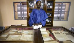 ** FILE ** An unidentified worker looks after some of the 20,000 preserved ancient Islamic manuscripts that rest in air-conditioned rooms at the Ahmed Baba Institute in Timbuktu, Mali, in 2004. (AP Photo/Ben Curtis)