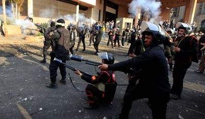 Police fire tear gas at protesters Tuesday in front of the Semiramis Hotel (background) in Cairo. Since Saturday, the hotel has been on the front line of clashes between police and angry youths. (Associated Press)