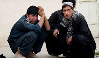 An Afghan policeman (left) mourns after a police truck was hit by a roadside bomb in Kandahar, Afghanistan, on Jan. 27, 2013. The truck was packed with officers and detainees, several of whom were killed in the blast, officials said. (Associated Press)