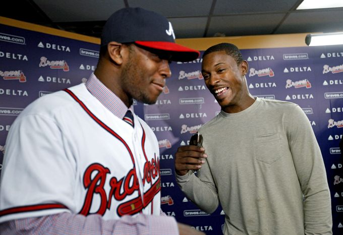 Justin Upton, left, acquired by the Atlanta Braves from the Arizona Diamondbacks in a seven-player deal last week, laughs with his brother B.J, Upton, right, who signed a five-year, $75.25 million contract with Atlanta in November, at Justin Upton's first news conference with his new team, Tuesday, Jan. 29, 2013, in Atlanta. (AP Photo/David Goldman)