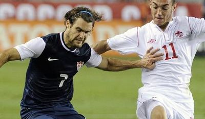 United States' Graham Zusi (7) holds off Canada's Russell Tiebert (11) in the first half of an exhibition soccer match Tuesday, Jan. 29, 2013, in Houston. (AP Photo/Pat Sullivan)