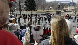A woman carries a poster promoting a gun control movement during a rally on the steps of the Colorado State Capitol, in Denver, Monday, Jan. 28, 2013. Colorado's long-anticipated gun control debate is getting under way, with some Democrats planning to pursue gun control measures including expanded background checks and a possible statewide assault-weapons ban. At the same time, Republicans were arguing Monday for a bill designed to allow school employees to carry concealed weapons at work. (AP Photo/Brennan Linsley)